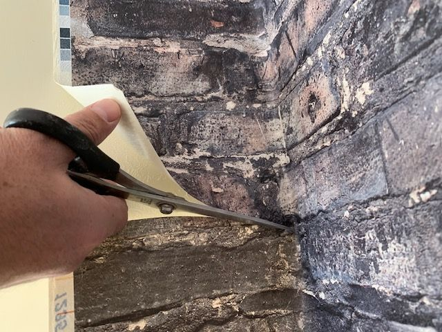 吊戸棚の壁紙をハサミでカット