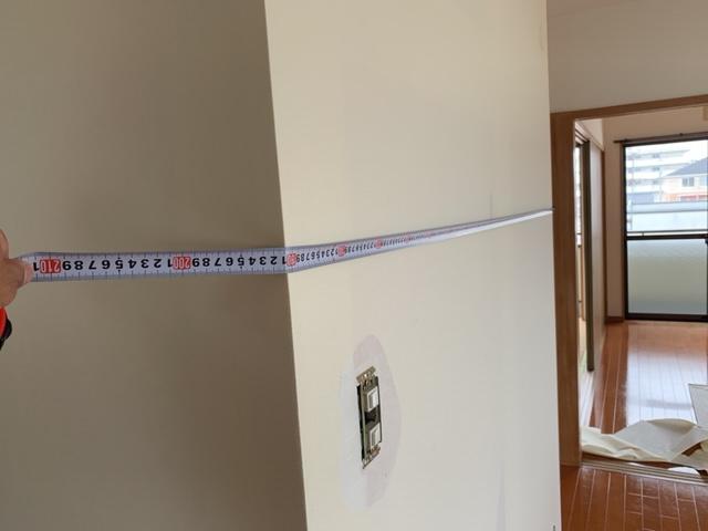壁をメジャーで測る