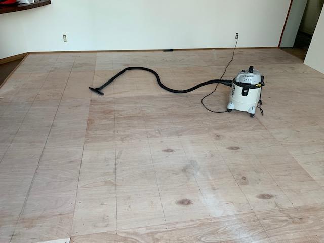 掃除機で床のゴミやホコリを取り除く