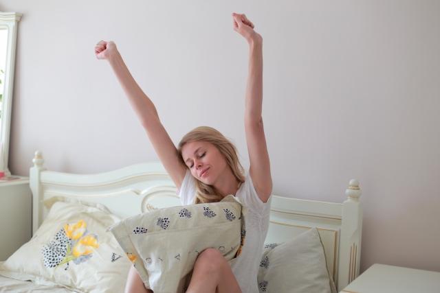 ベッドルームで背伸びする女性