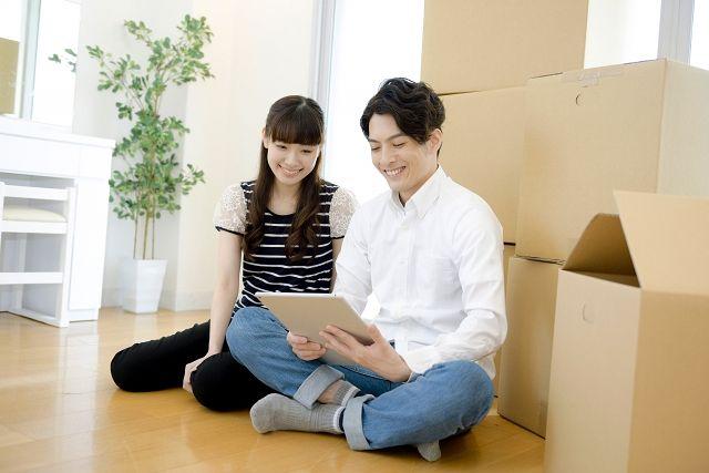 引っ越し作業中にタブレットを扱うカップル